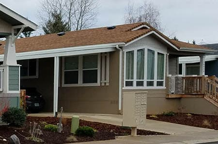 Manufactured home with a big bay window. The home is located in in a manufactured home community in Oregon.